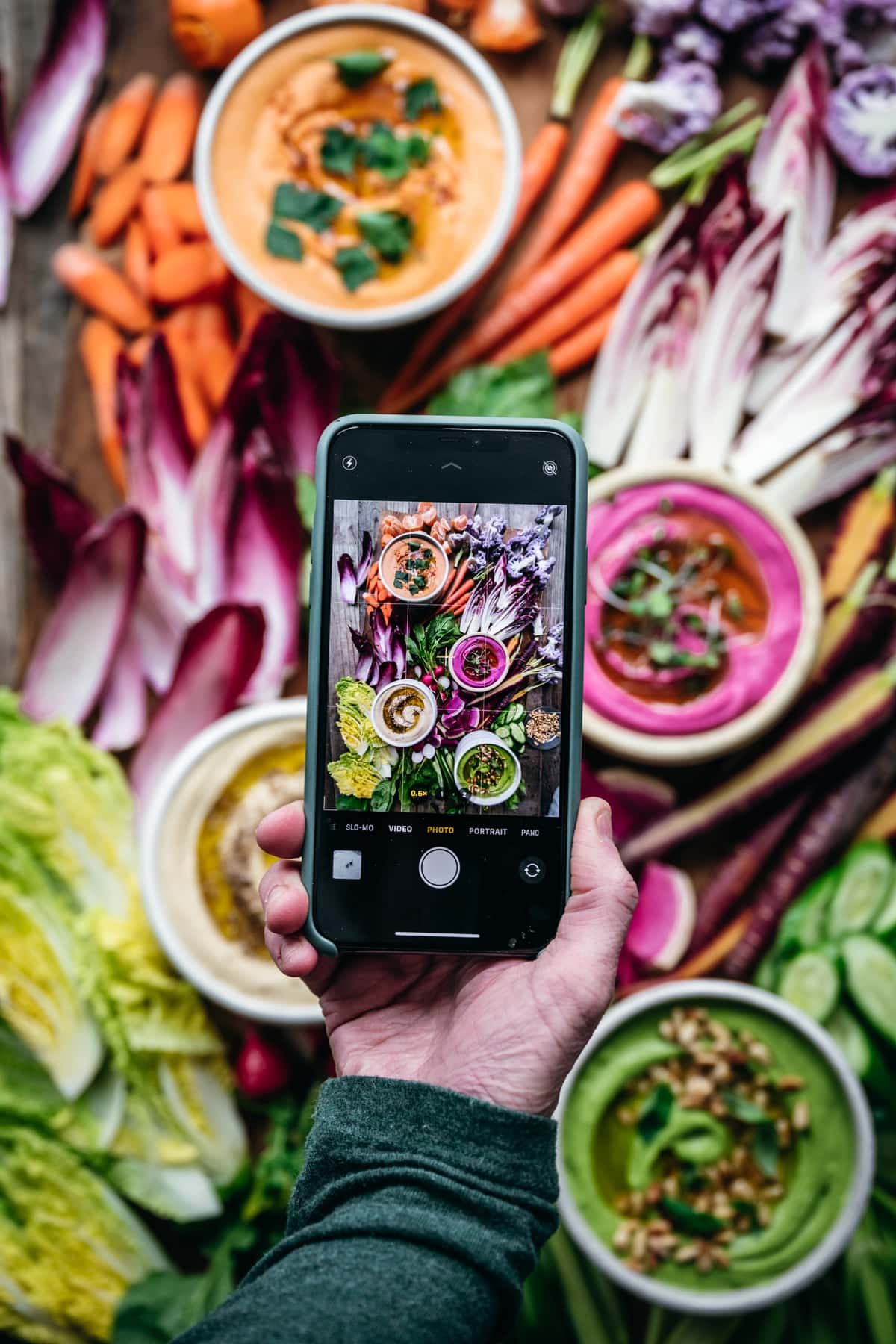 overhead view of person holding phone over colorful hummus platter