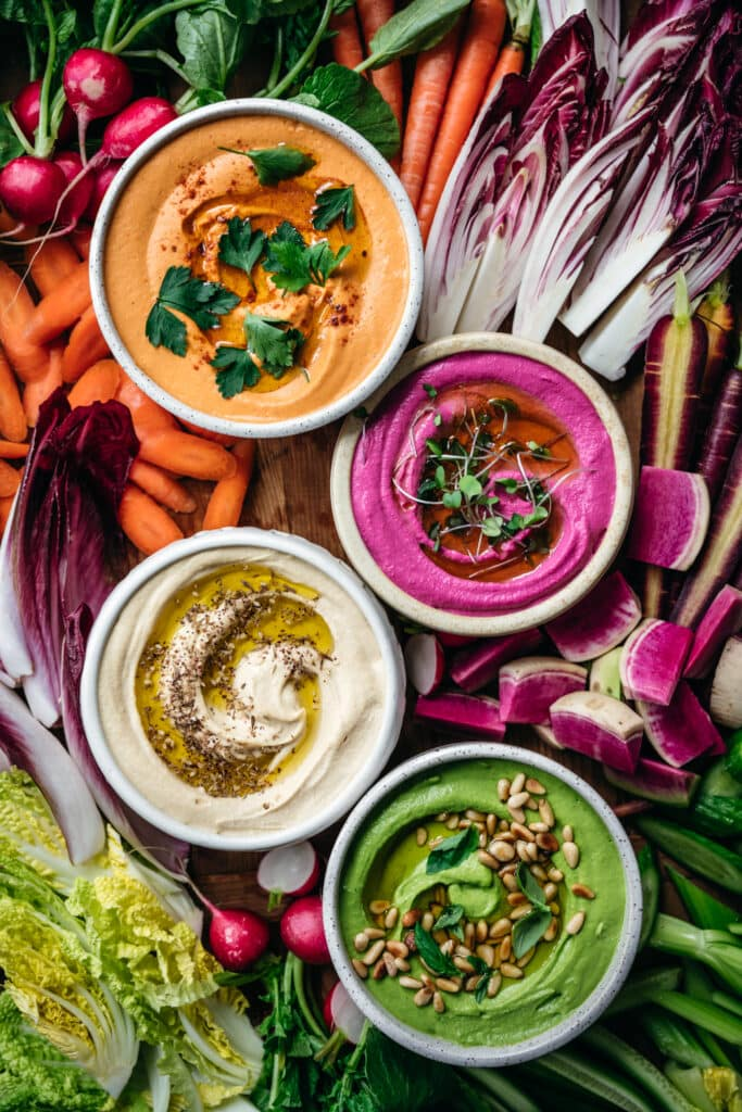overhead view of homemade hummus 4 ways with colorful vegetables on a platter