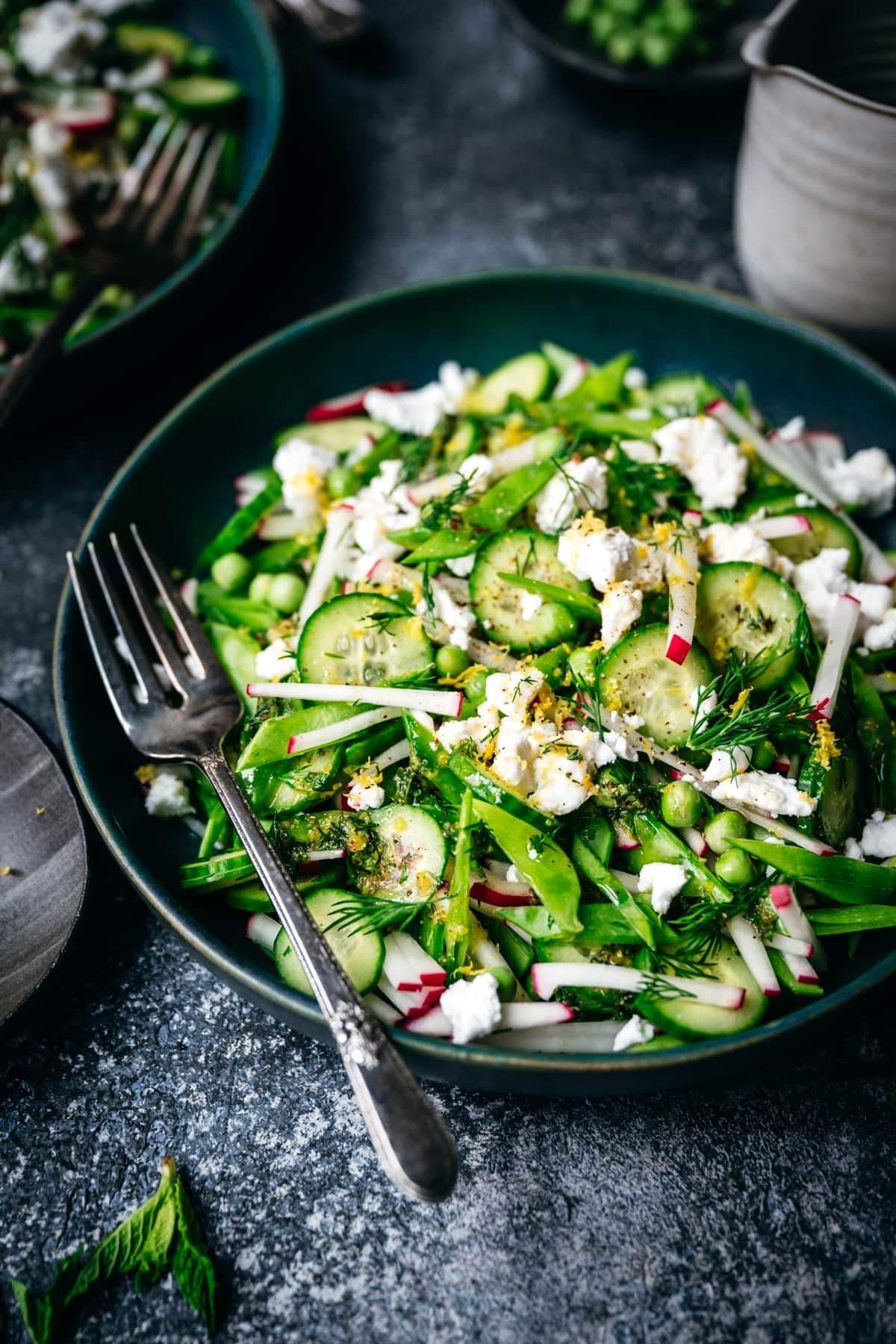 close up side view of snow pea salad with radishes, cucumber and vegan feta in blue bowl