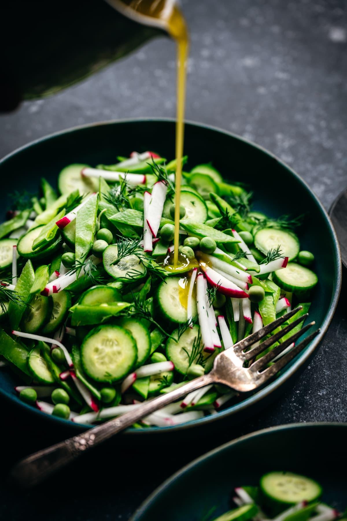 pouring lemon vinaigrette onto fresh pea salad