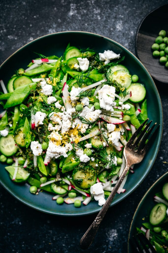 close up overhead view of snow pea salad with radishes, cucumber and vegan feta in blue bowl