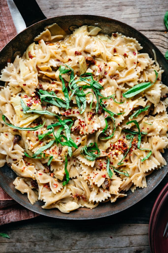 overhead view of vegan sun-dried tomato pasta with basil and red pepper flakes in pan