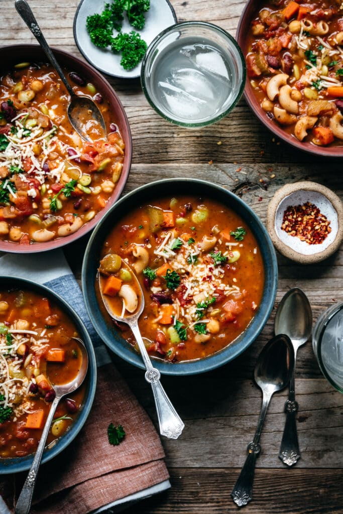 overhead view of vegan minestrone soup in blue bowls on wood table