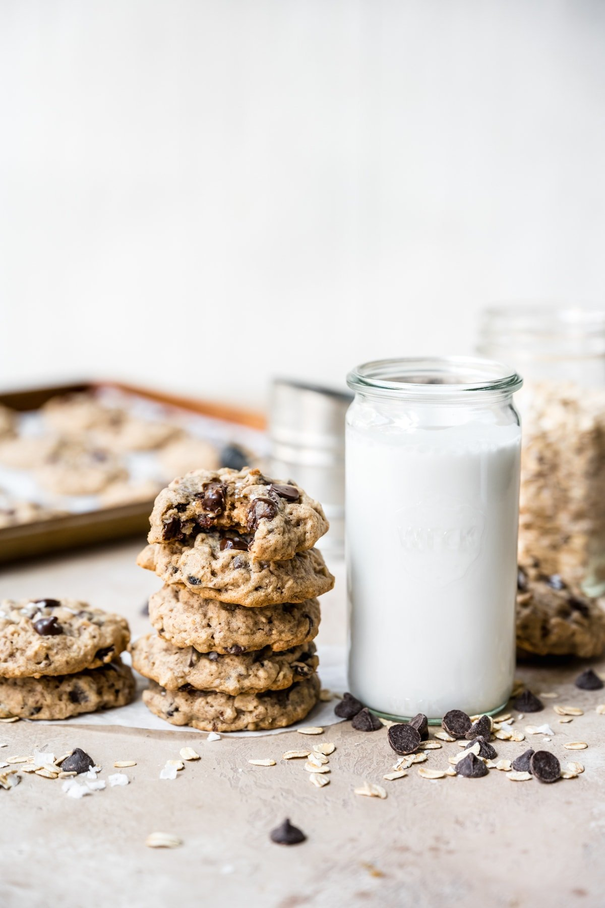 side view of stack of oatmeal raisin chocolate chip cookies next to a glass of milk