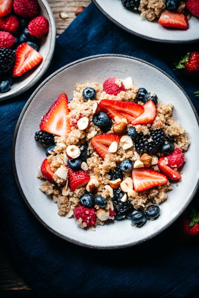 close up overhead view of vegan breakfast quinoa in bowl with berries
