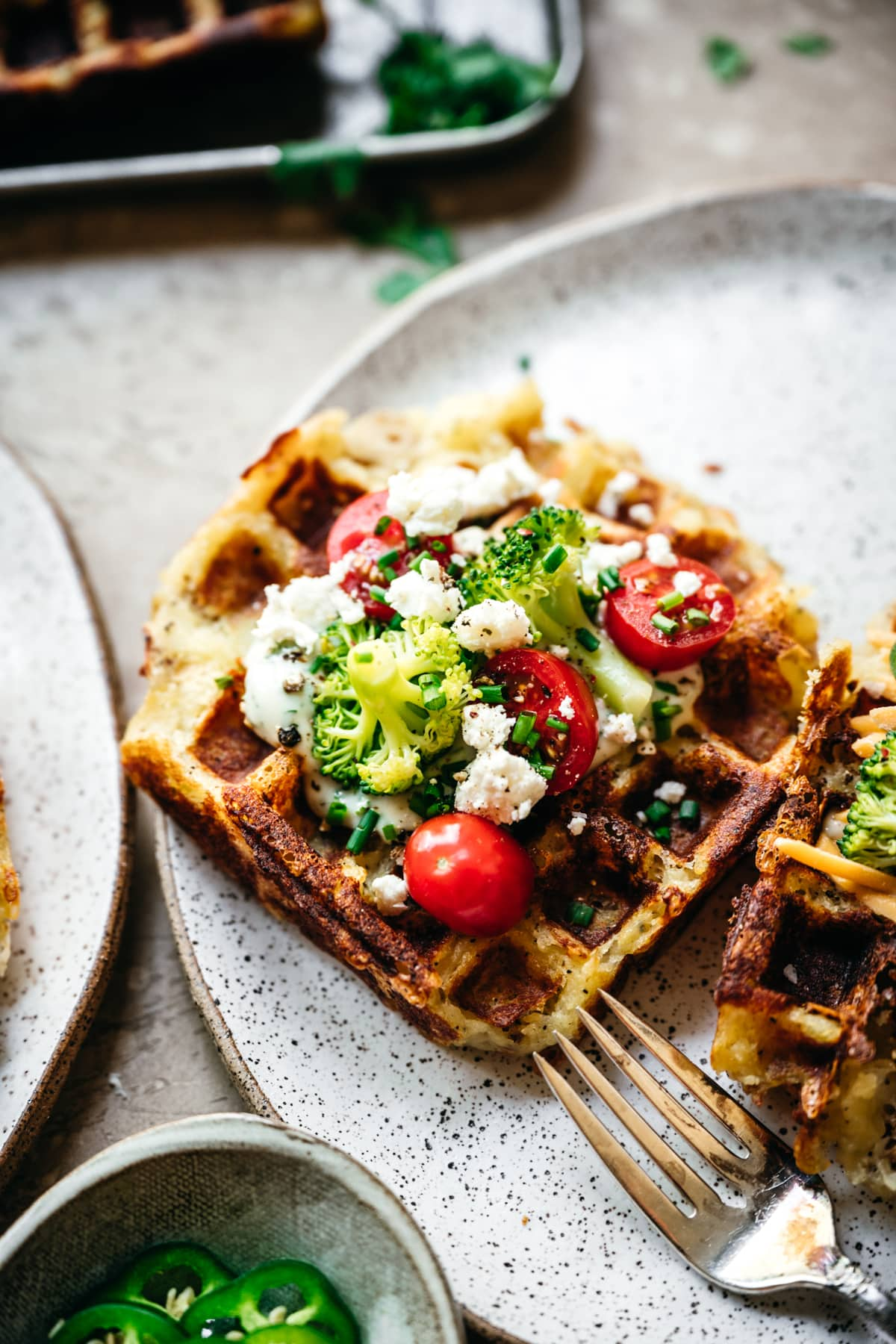 close up side view of mashed potato waffle topped with broccoli, tomatoes and cheese