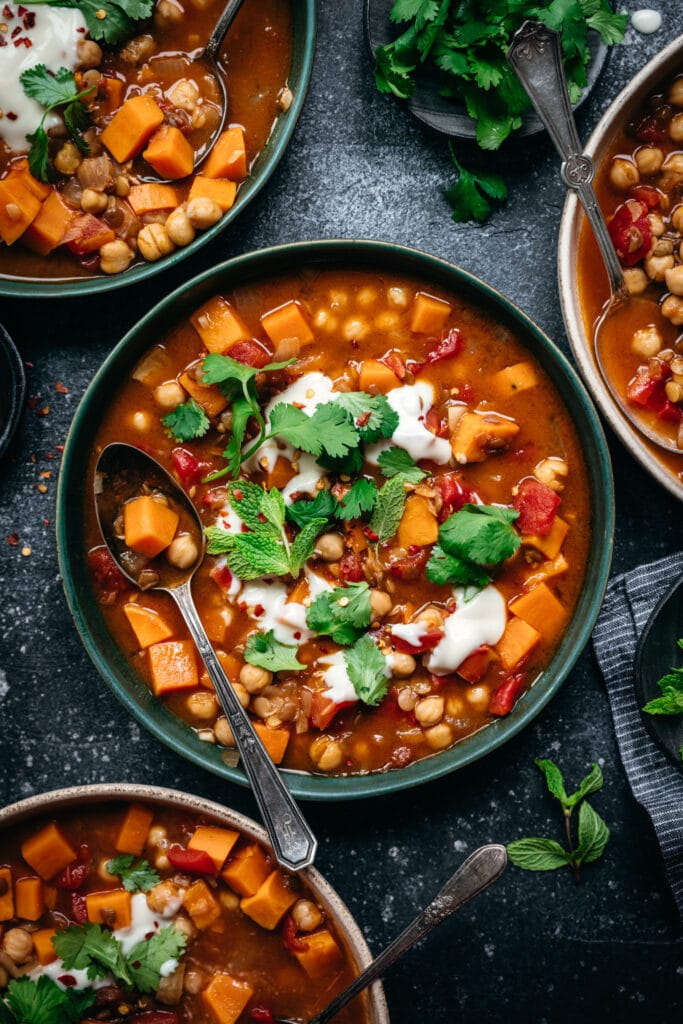 overhead view of vegan Moroccan chickpea lentil stew in bowl with spoon