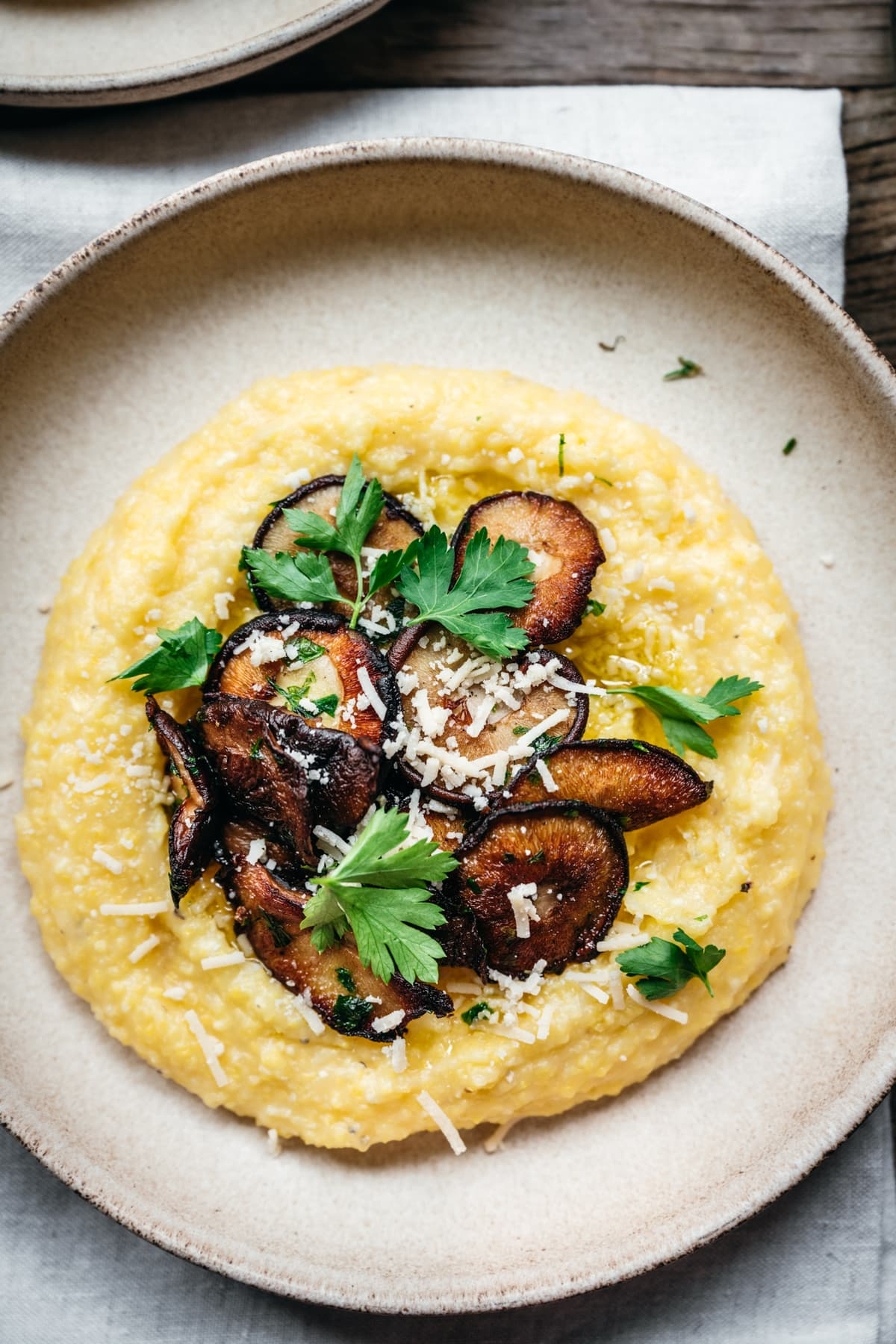 close up overhead view of vegan polenta with pan seared mushrooms and herbs