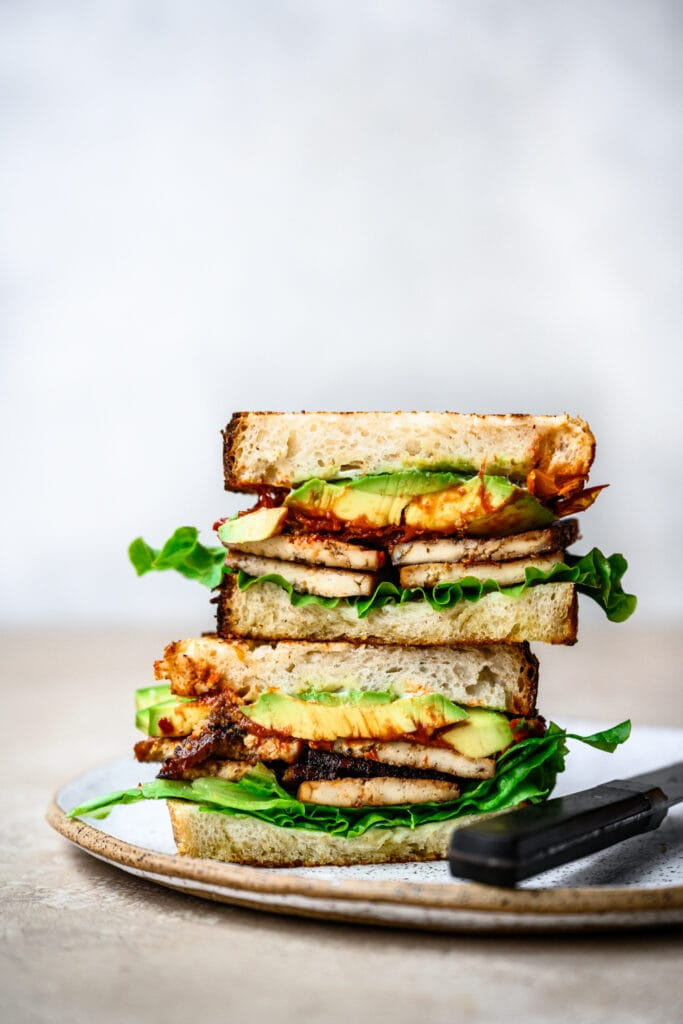 side view of vegan blt cut in half on plate