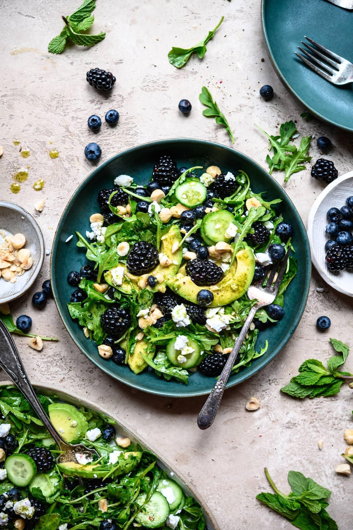 overhead view of blackberry avocado arugula salad in blue bowl