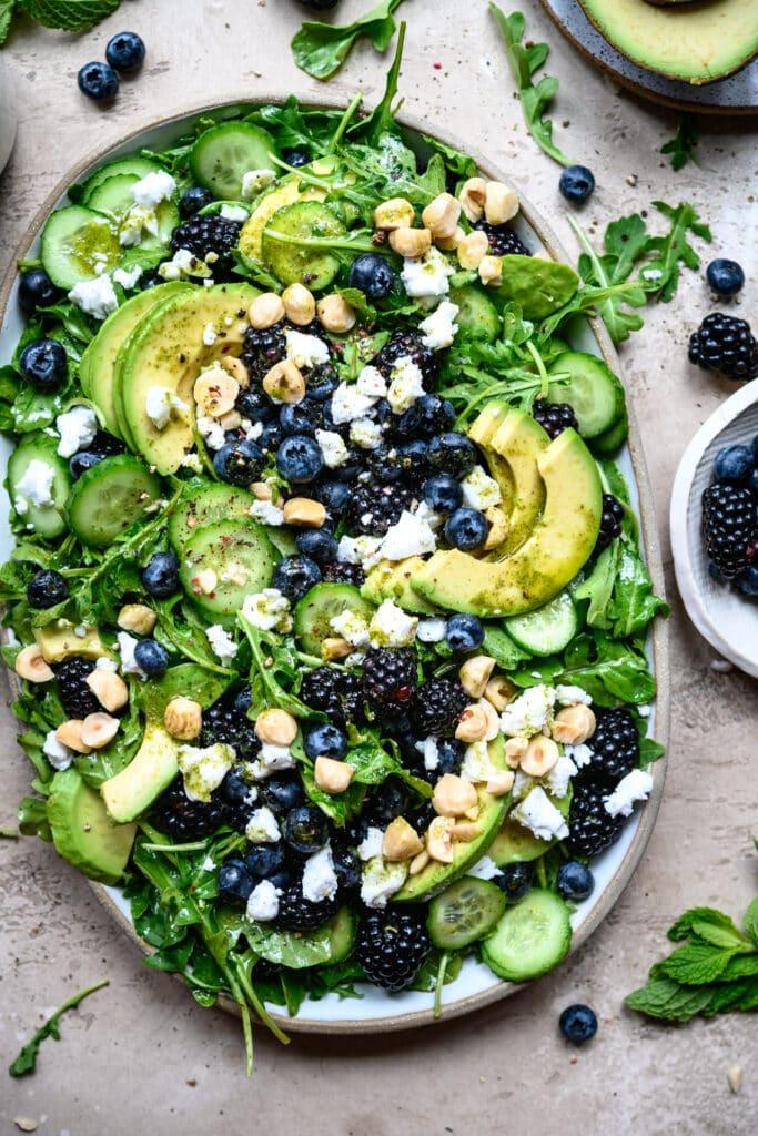 overhead view of blackberry avocado arugula salad on a white platter