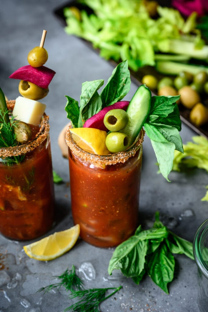 side view of vegan bloody mary in tall glass with garnishes