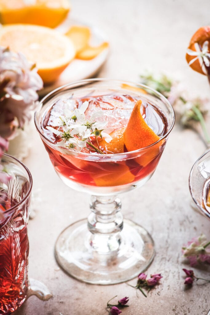 close up side view of backlit cherry negroni cocktail with orange peel and flowers