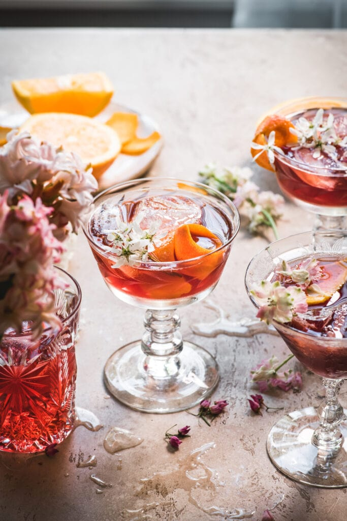 side view of backlit cherry negroni cocktail with orange peel and flowers