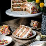 Funfetti cake on a cake stand with slices of cake on plates below.