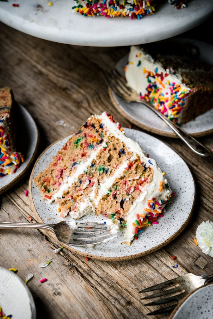 side view of a slice of vegan gluten free funfetti vanilla cake on a small plate