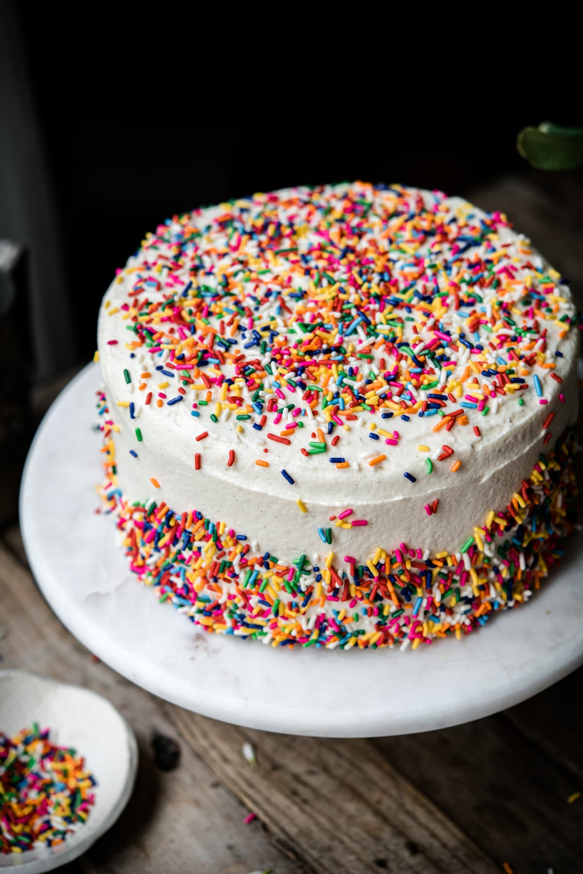 side view of vegan funfetti birthday cake with vanilla frosting