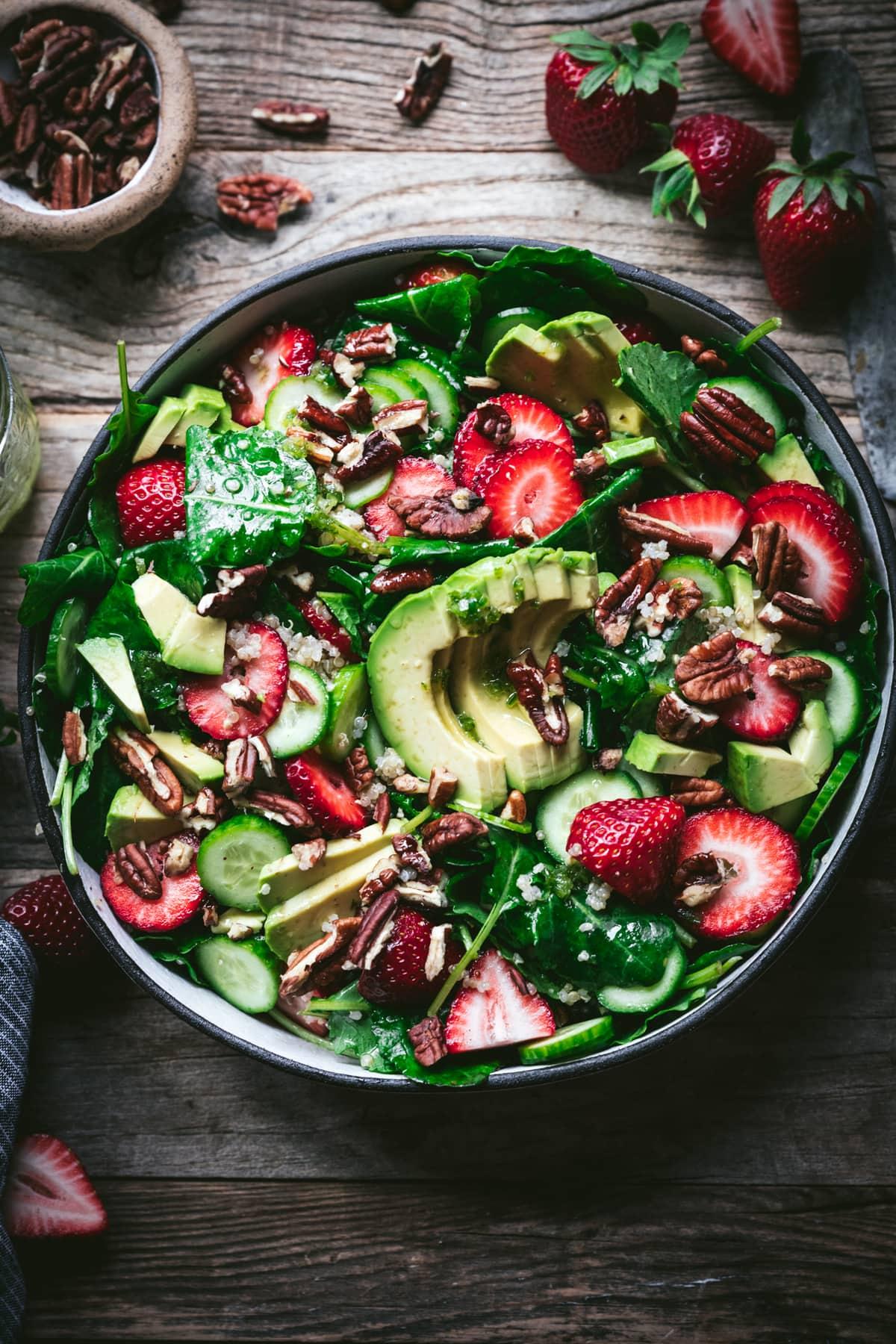 overhead view of strawberry quinoa avocado salad in white bowl