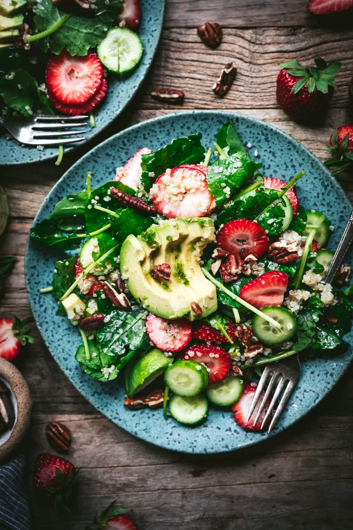 overhead view of strawberry quinoa avocado salad on blue plate