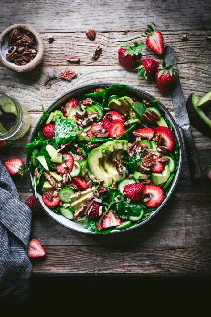 overhead view of strawberry avocado quinoa salad in a white salad bowl