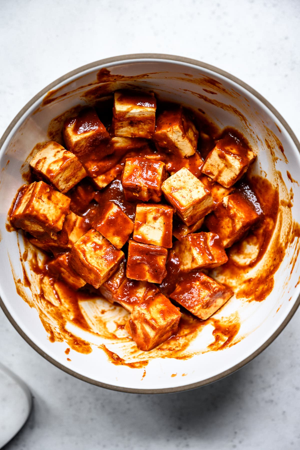 overhead view of tofu cubes in barbecue marinade