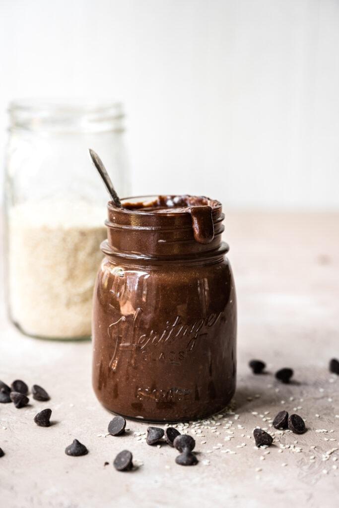 side view of homemade chocolate tahini in a glass jar