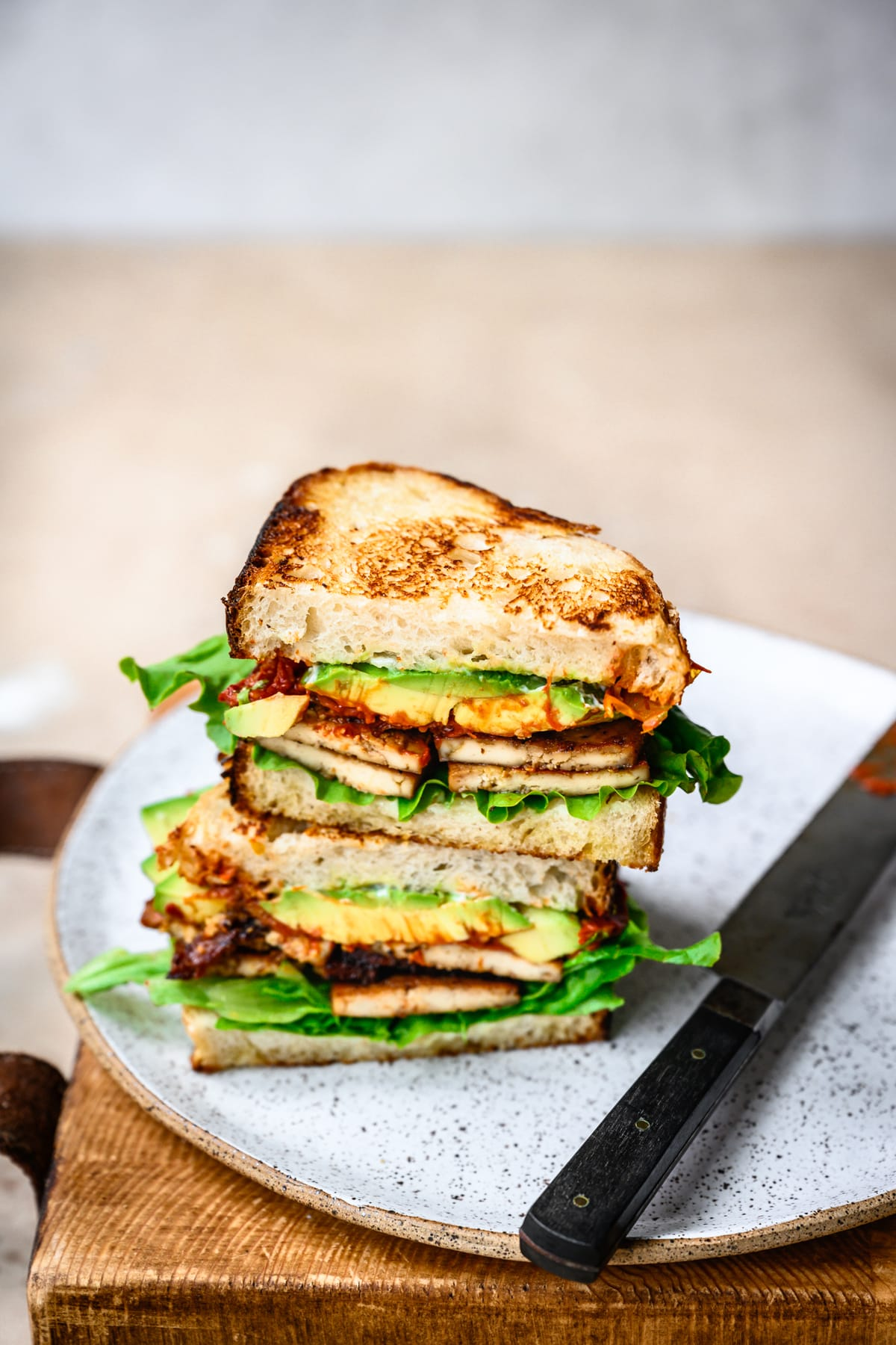 side view of vegan BLT with avocado cut in half and stacked