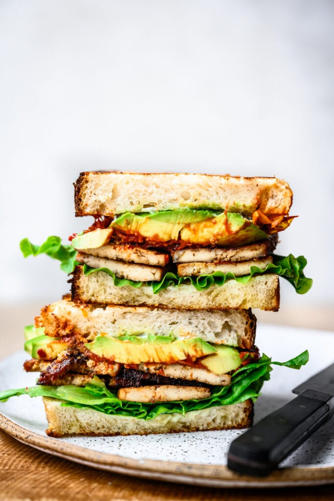 close up view of vegan BLT sandwich cut in half and stacked on plate