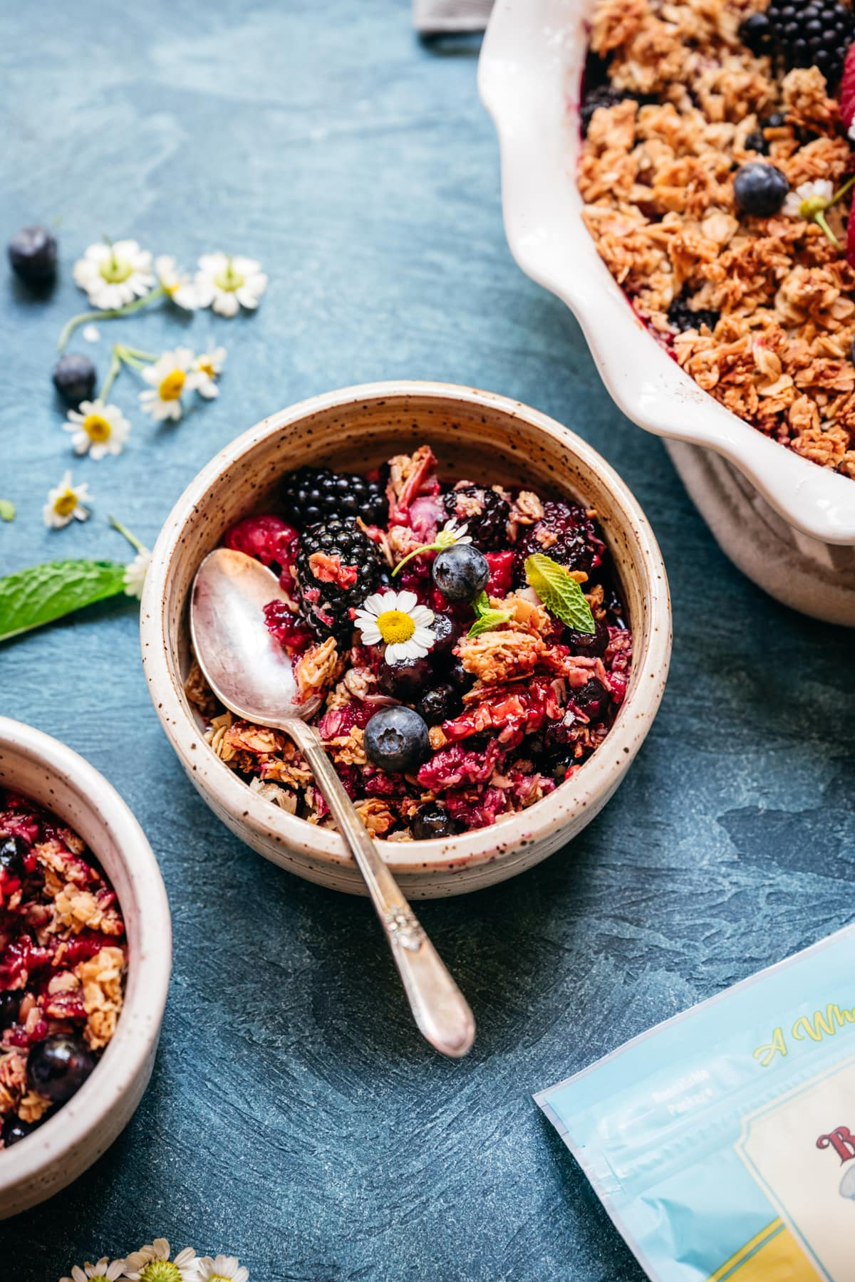 triple berry granola crisp in a small bowl with spoon