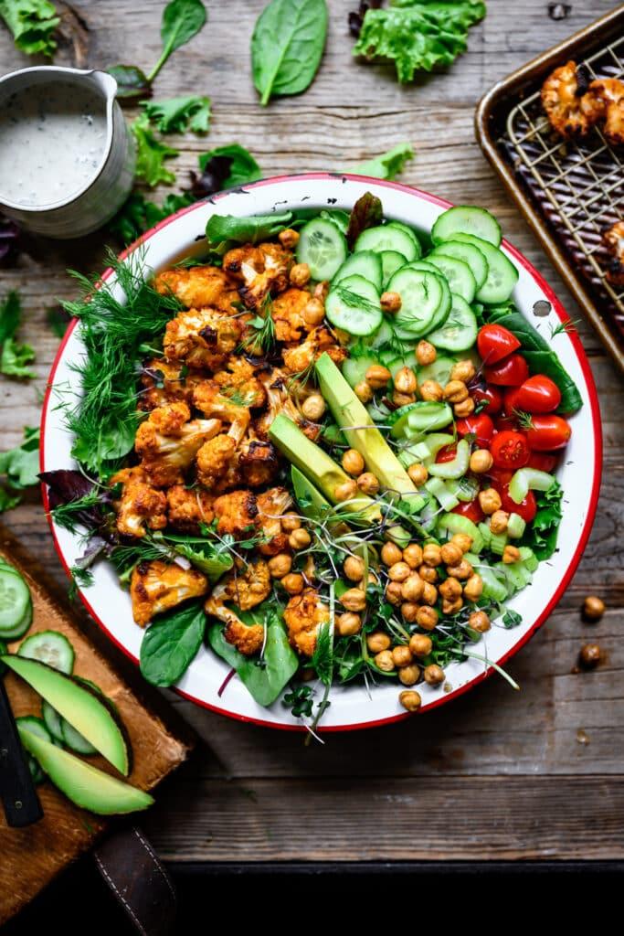 overhead view of vegan buffalo cauliflower salad with ranch and avocado