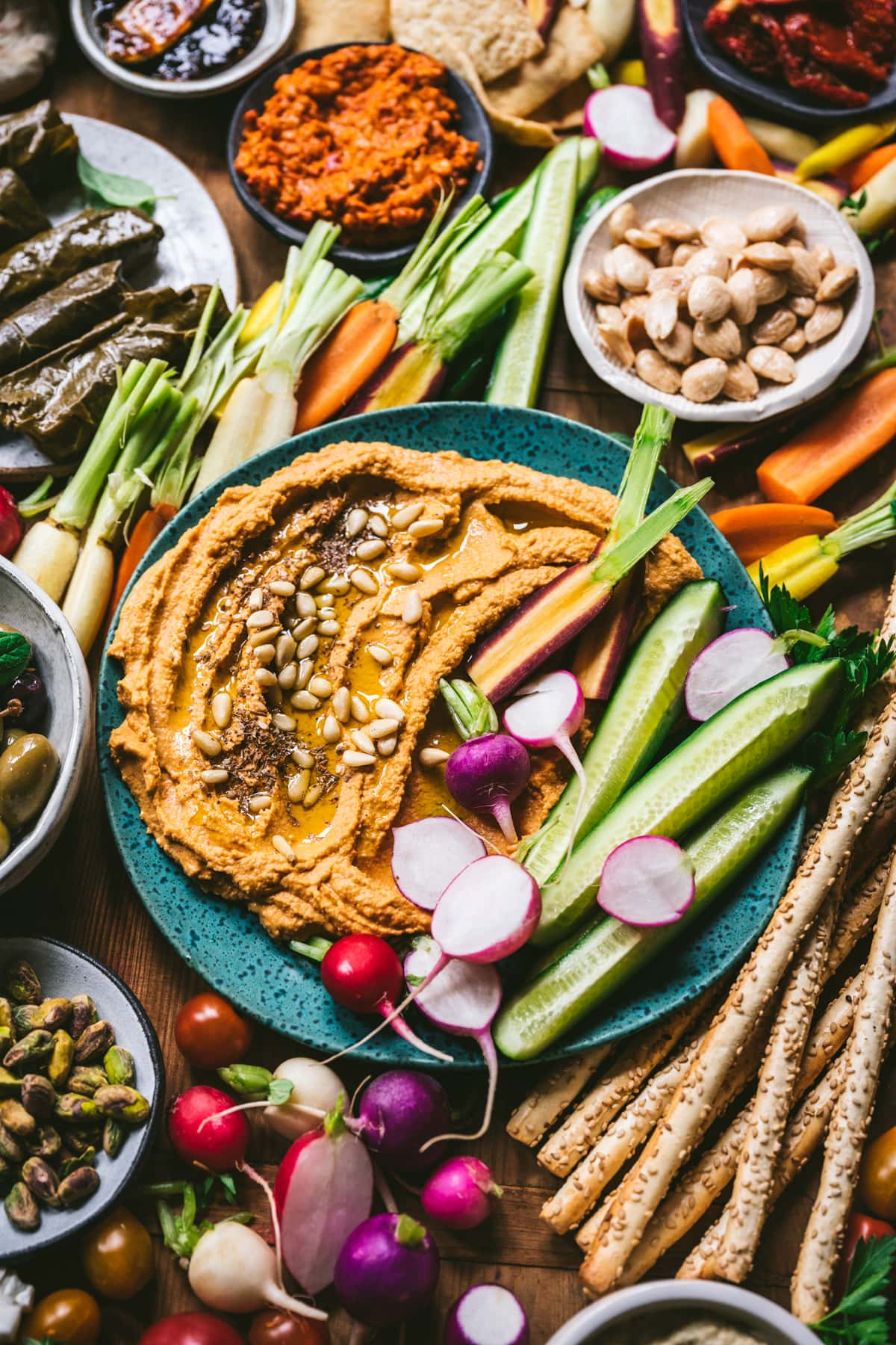 close up view of roasted red pepper hummus with fresh vegetables for dipping