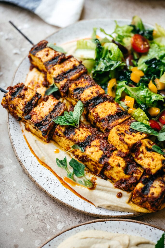 Side view of Mediterranean tofu kebabs over hummus with a salad