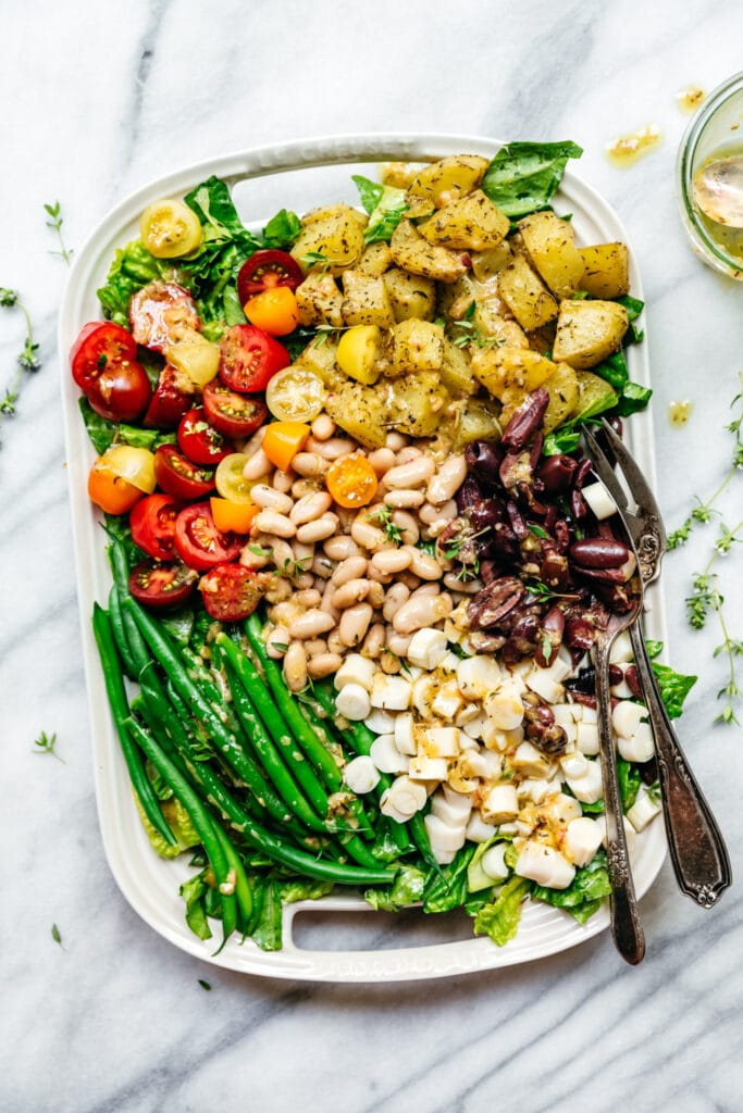 overhead view of vegan nicoise salad with white beans on a white platter