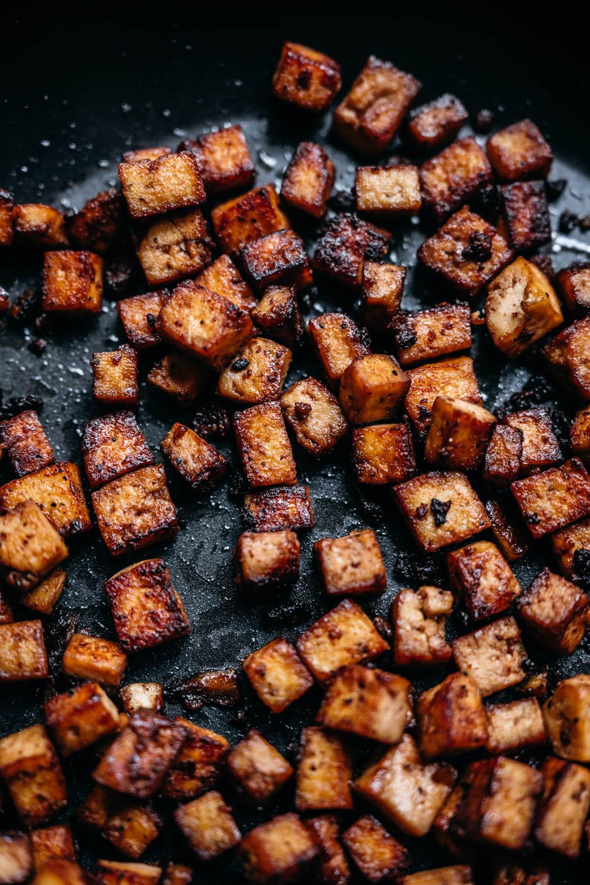 close up view of vegan tofu bacon bites in a pan.