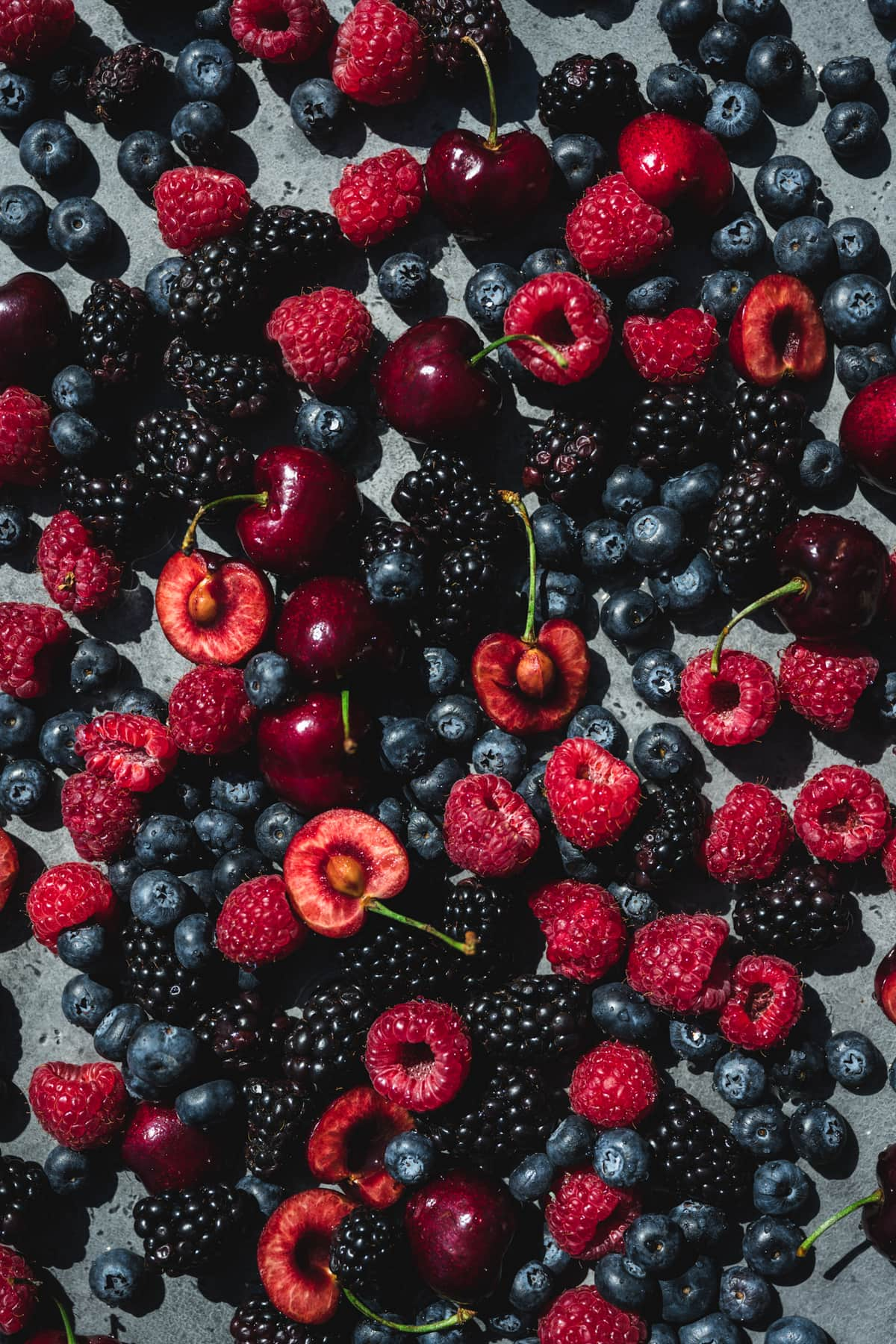 overhead view of mixed fresh berries in direct sunlight