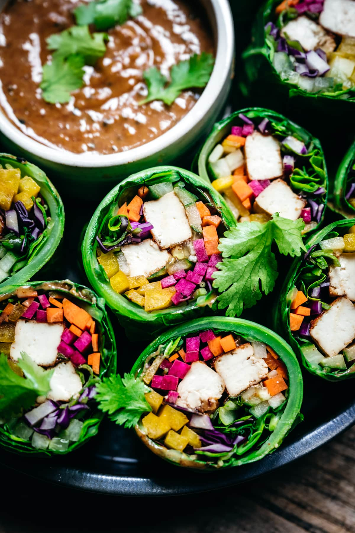Close up view of vegan collard green wraps with vegetables and tofu cut in half with almond miso sauce