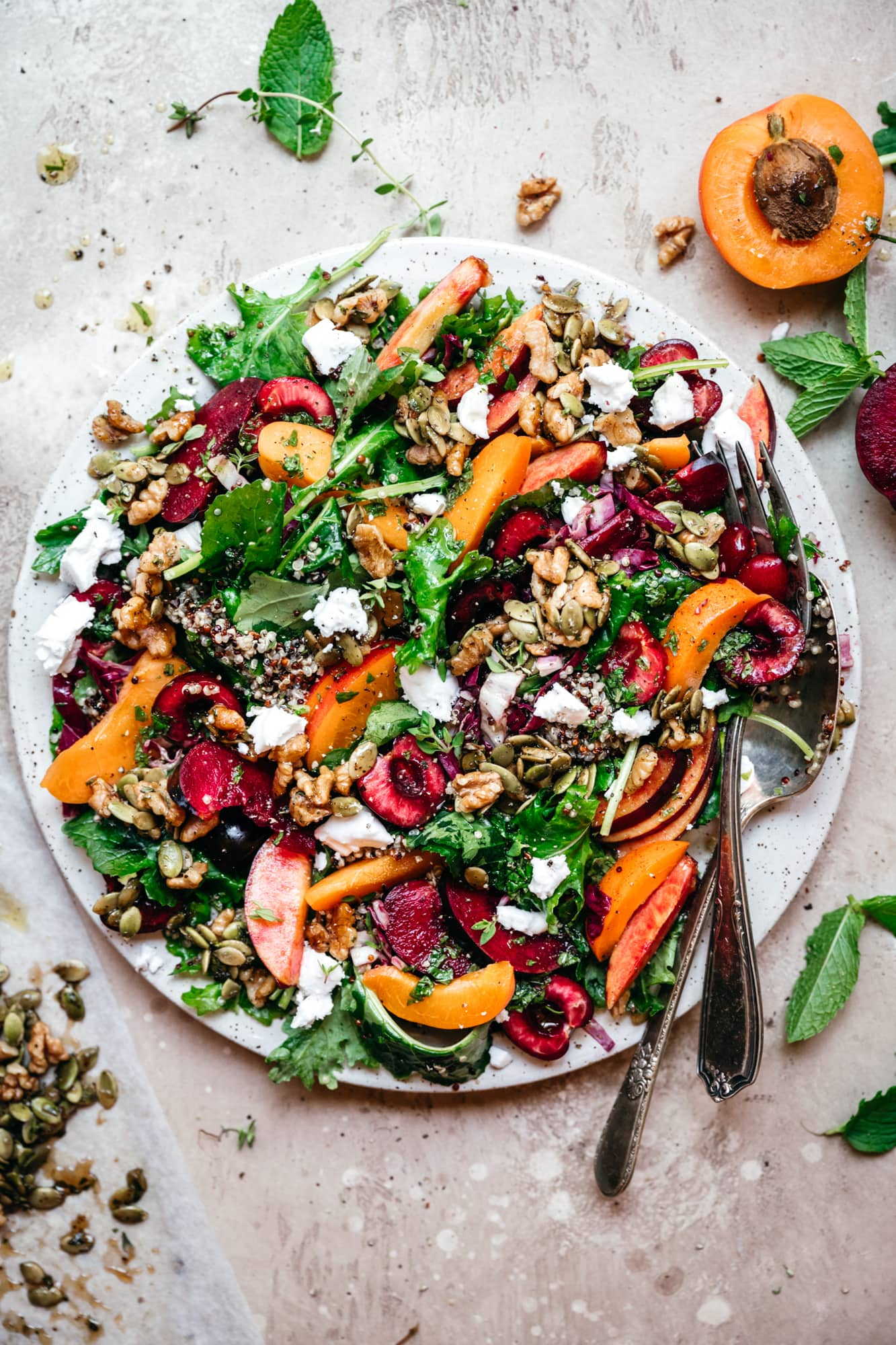 overhead view of kale and stone fruit salad with quinoa and feta on white plate
