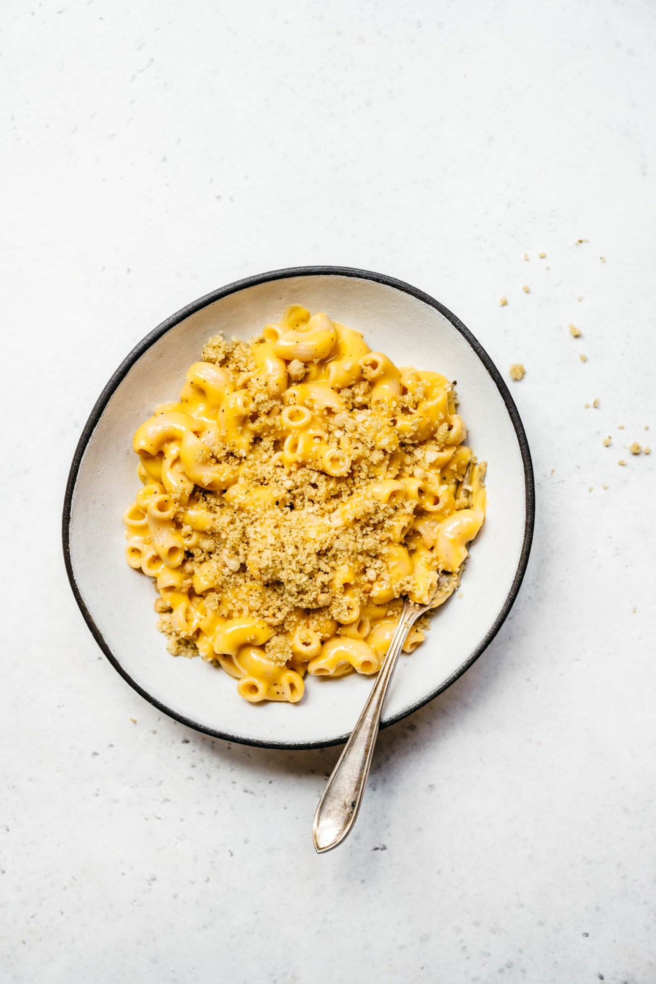 overhead view of easy vegan mac and cheese with breadcrumbs in white bowl