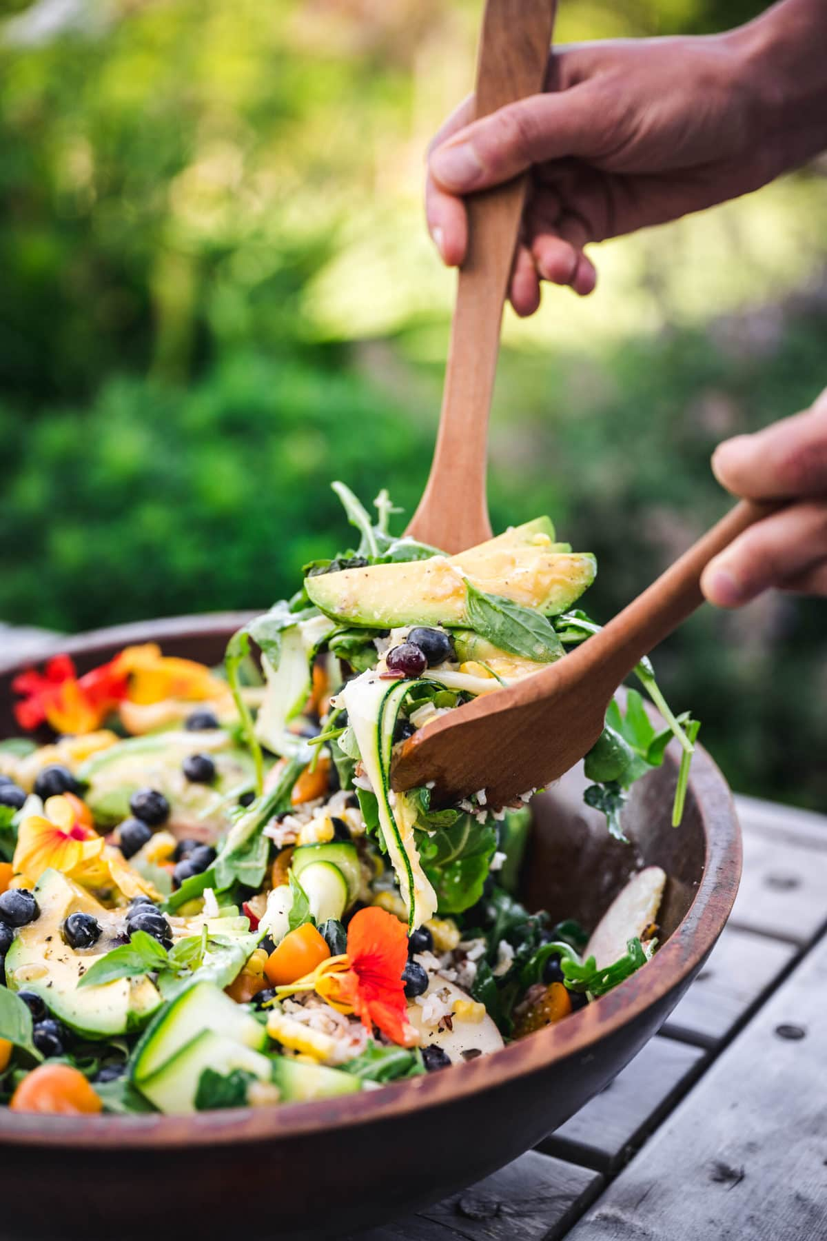 person using tongs to serve summer vegetable salad