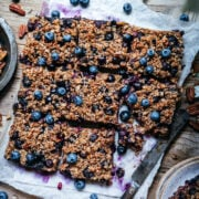 overhead view of vegan blueberry pecan baked oatmeal sliced into squares on wood cutting board