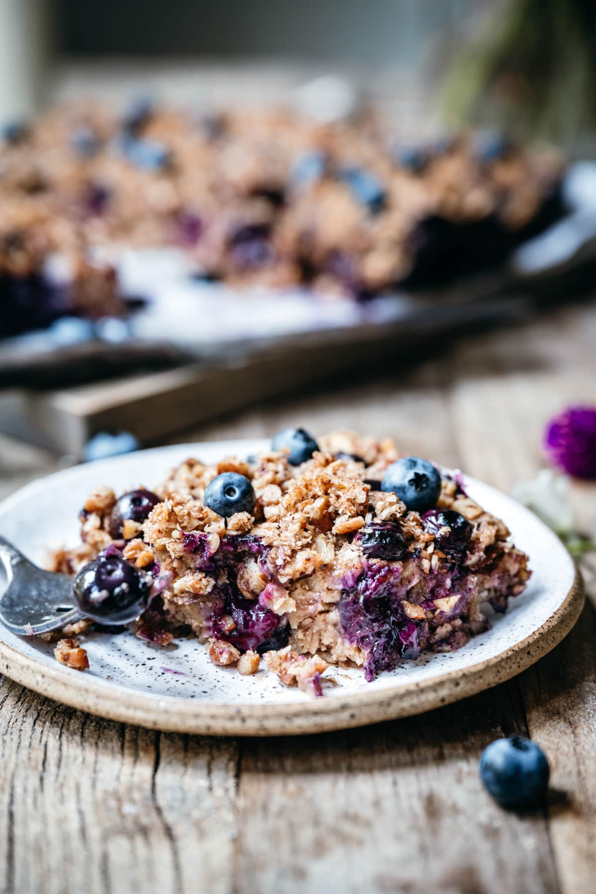 side view of slice of blueberry baked oatmeal on small plate