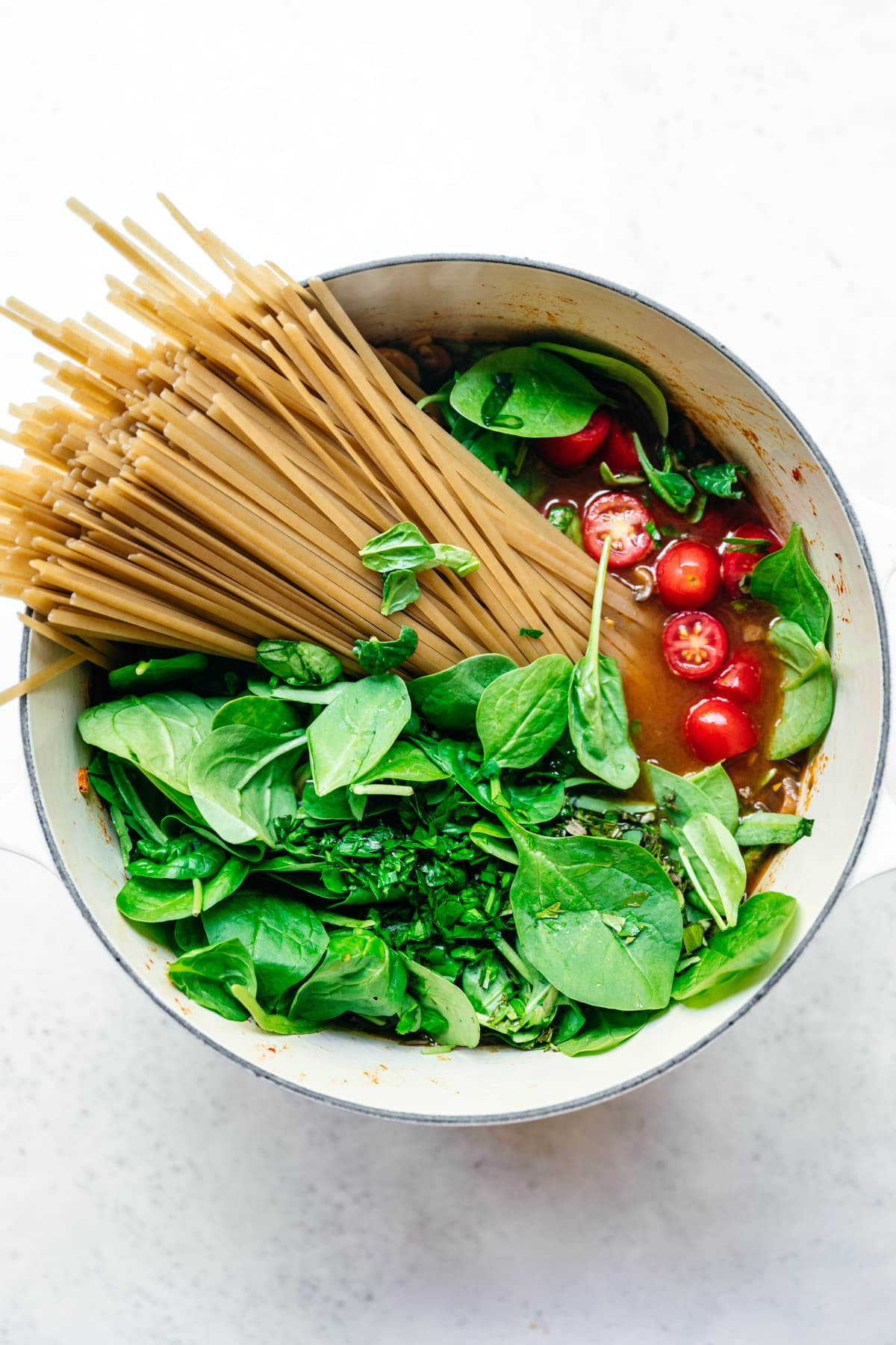 overhead view of ingredients for one pot pasta with spinach and tomatoes in a white dutch oven.