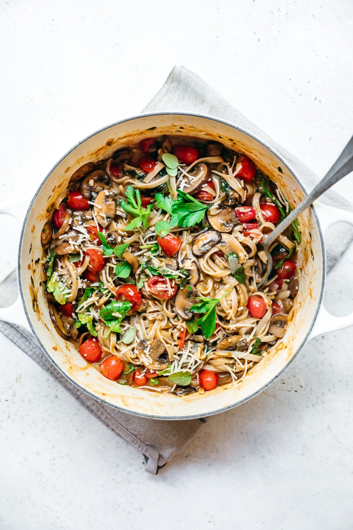 overhead view of vegan one pot pasta in a dutch oven with mushrooms and tomatoes.