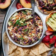 overhead view of vegan coleslaw in white bowl next to veggie burgers.