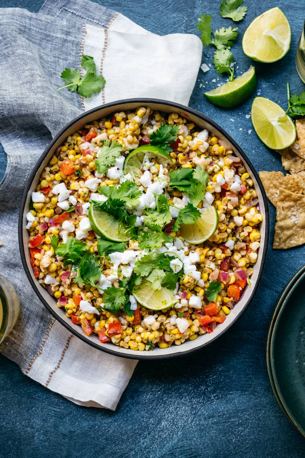 overhead view of bowl of vegan mexican street corn salad with limes and cilantro