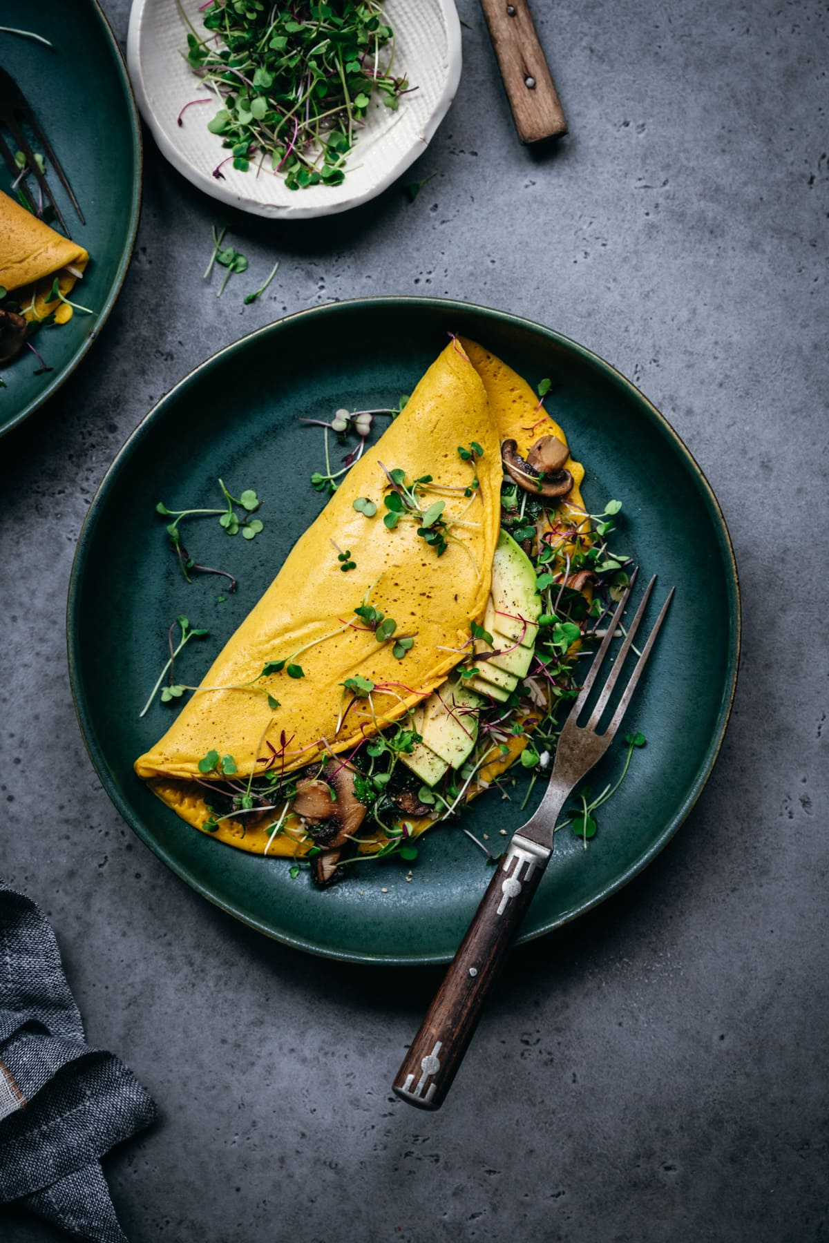 overhead view of vegan chickpea flour omelette with mushroom and spinach filling on teal plate.
