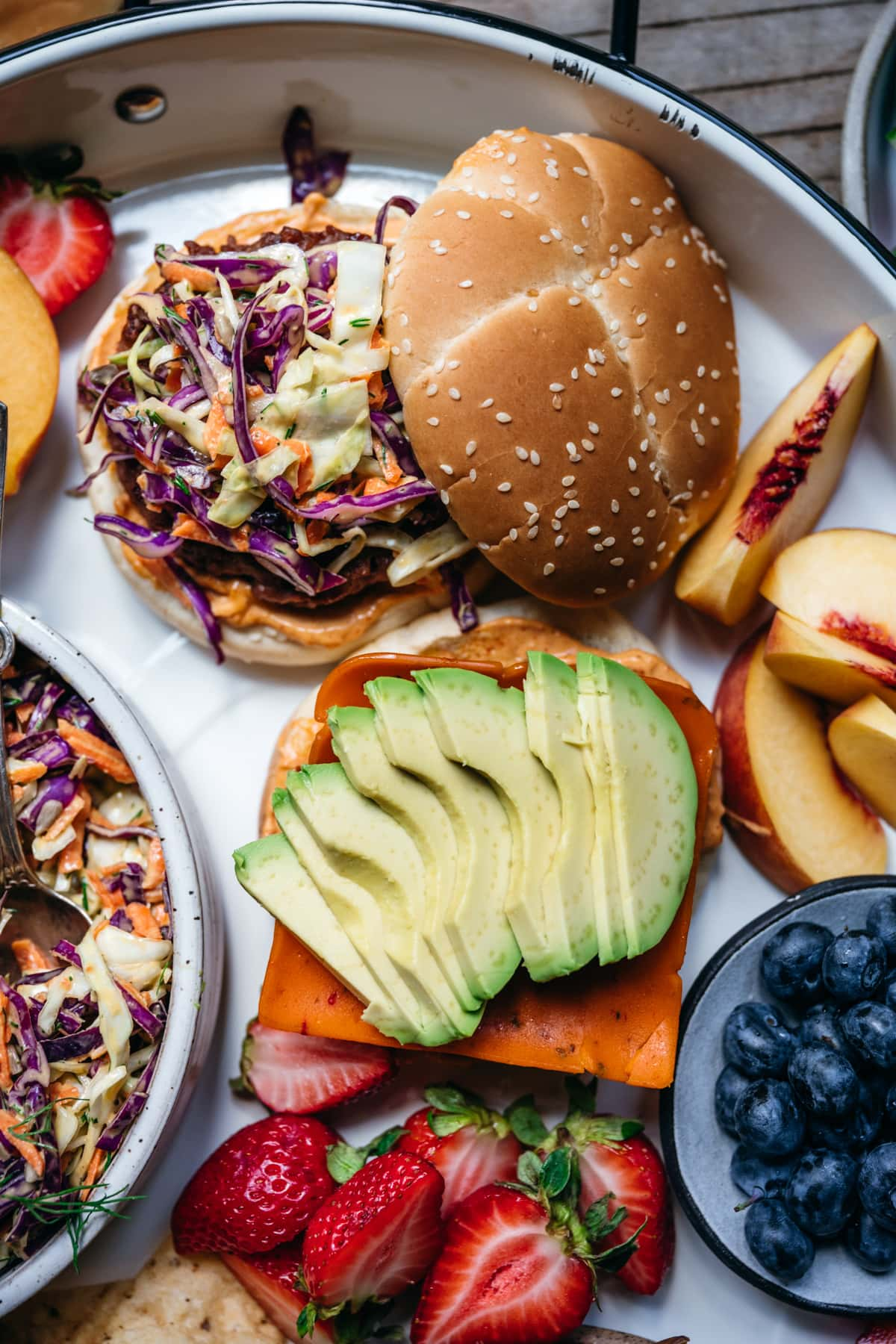 overhead view of two open-faced veggie burgers with vegan cheese, avocado and coleslaw.