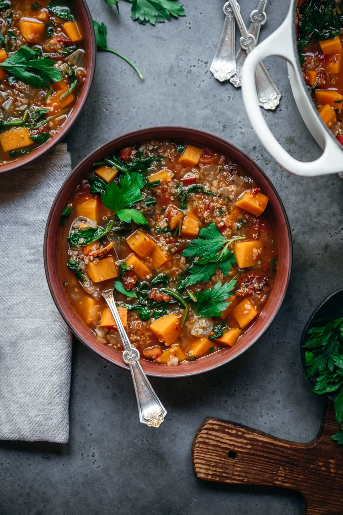 overhead view of quinoa vegetable soup with sweet potatoes in bowl with spoon.