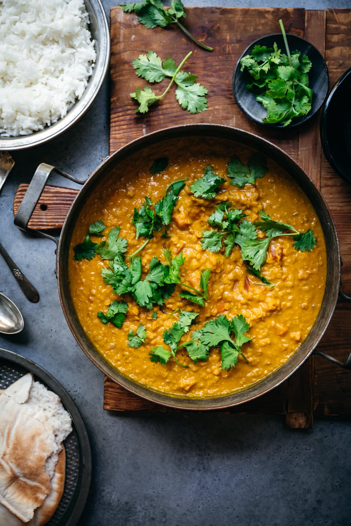 overhead view of a large pot of vegan masoor dal topped with fresh cilantro.