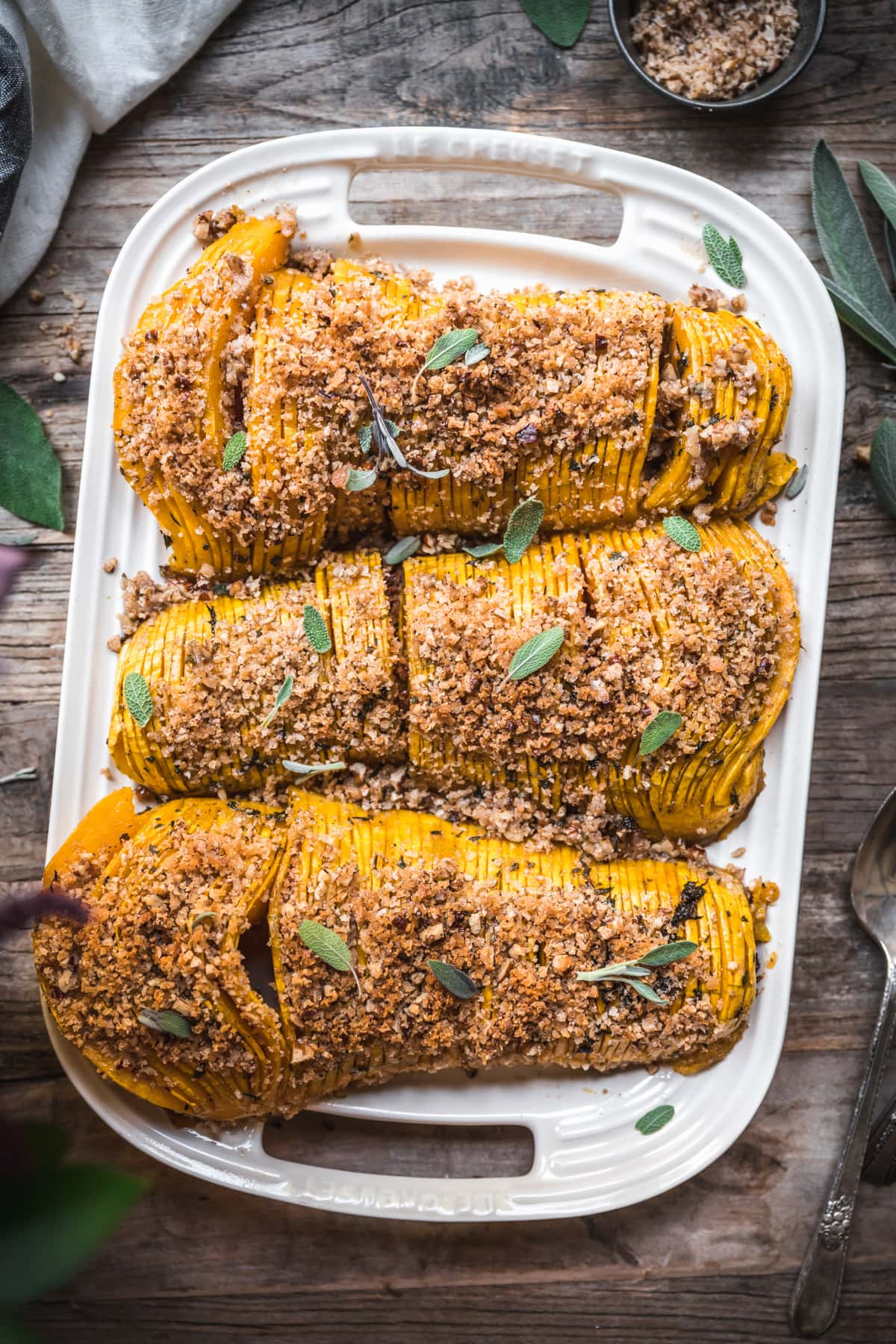 overhead view of hasselback butternut squash on a white platter topped with breadcrumbs.